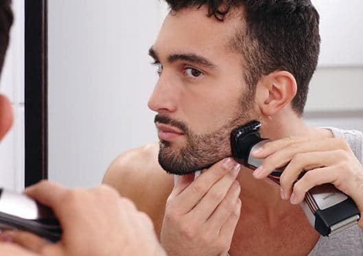 man using a beard trimmer in front of a mirror