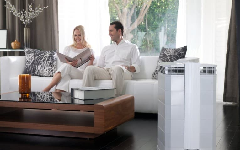 a couple sitting on a couch beside an air purifier