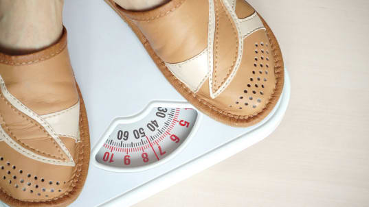 woman getting her weight on a bathroom scale
