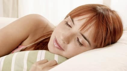 woman sleeping with a striped bedsheet