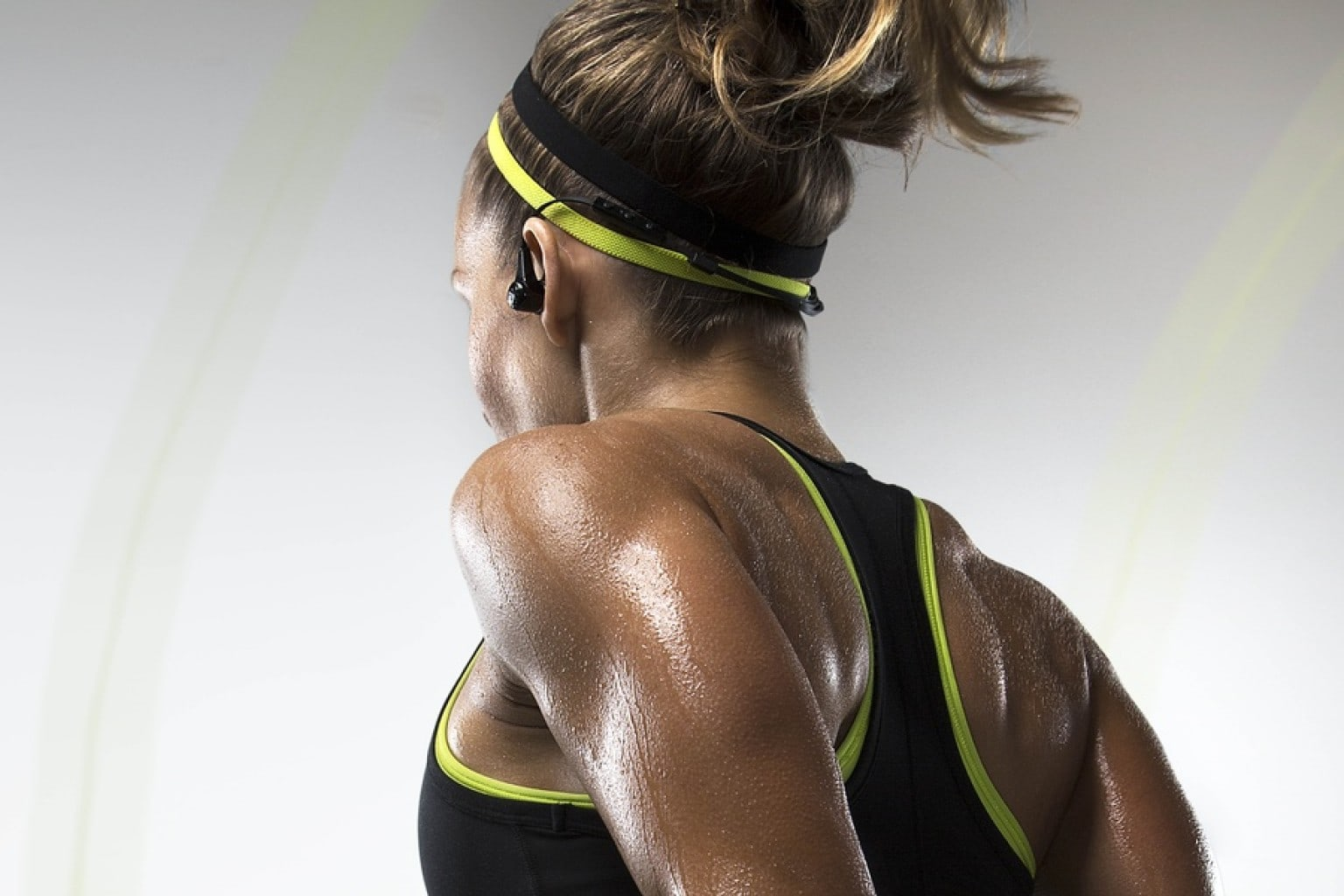 woman using a bluetooth earphone while working out