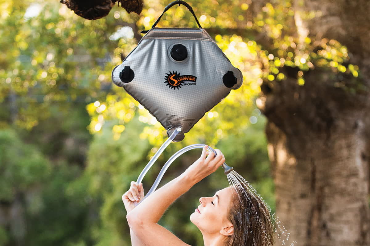 woman taking a shower using a camping shower