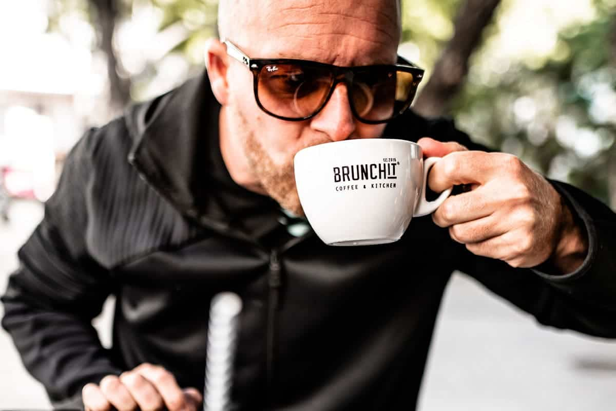 man sipping a cup of coffee