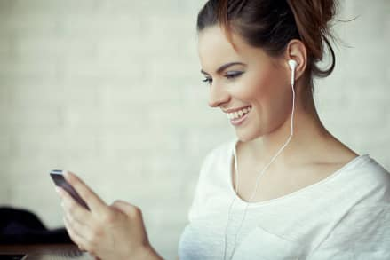 woman using her earbuds while holding her phone