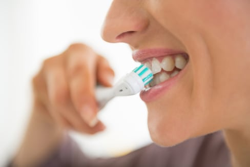 woman brushing her teeth with bristles at a 45-degree angle
