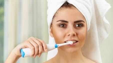 woman brushing using an electric toothbrush