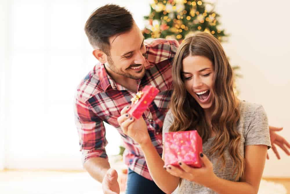 man surprising a woman with a gift