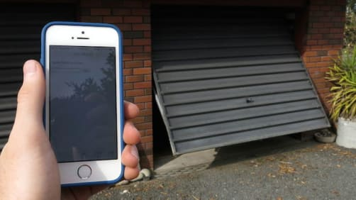 holding an iphone in front of the garage