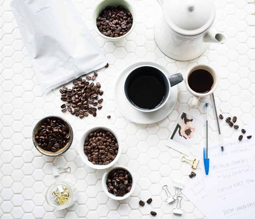 a cup of coffee and cups of coffee beans at the table
