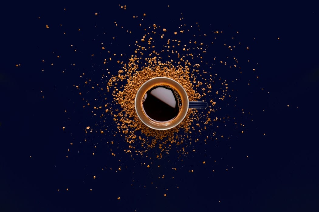 a cup of coffee and ground coffee beans