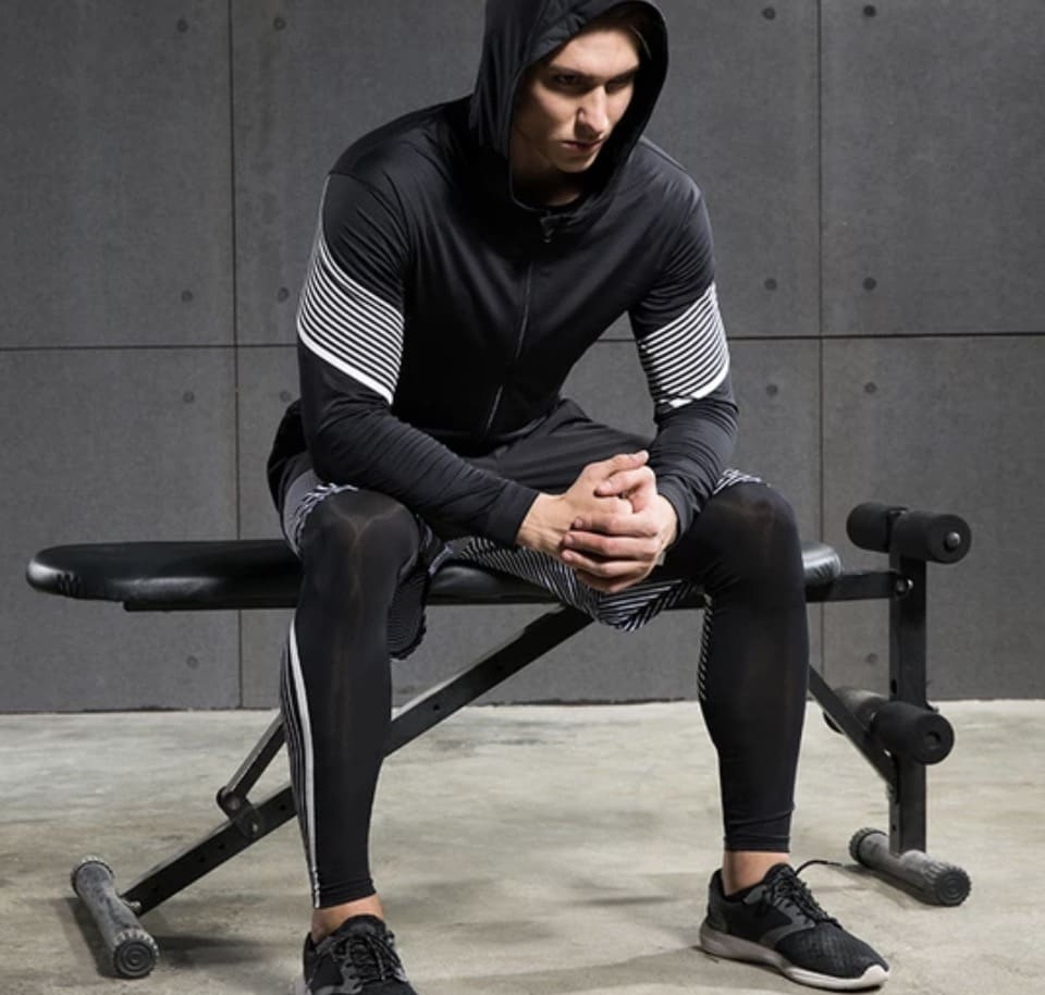 man sitting on a workout bench wearing a black compression pants