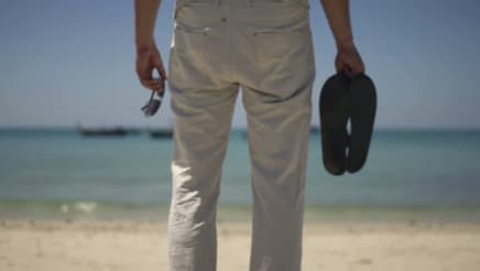 man holding a pair of sandals at the beach