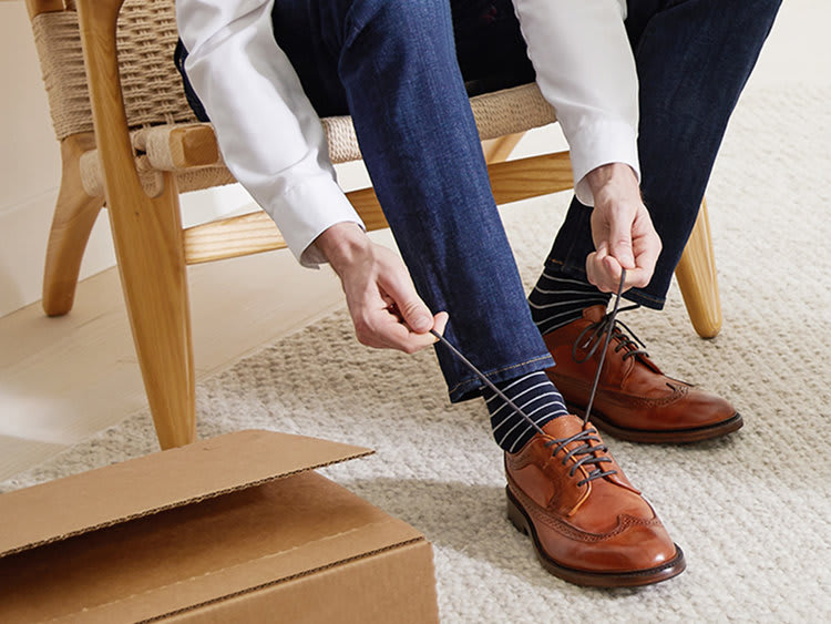 man wearing a dress socks while tying his shoes