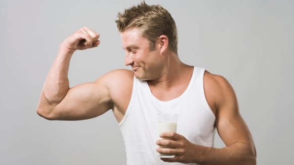 man wearing white undershirt and holding a glass of drink