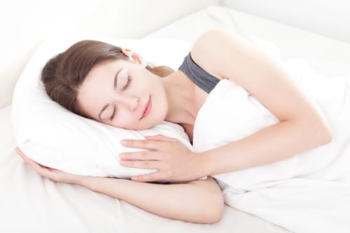 woman sleeping with pregnancy pillow