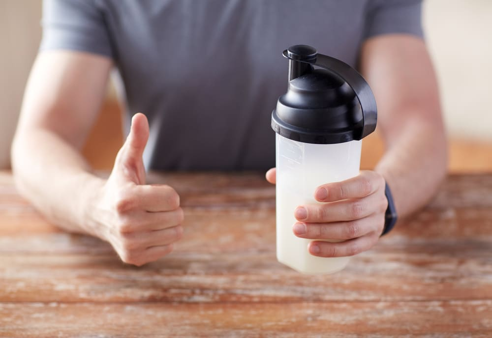 man holding a bottle of protein drink