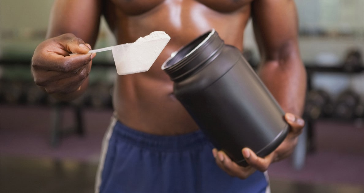 man getting a scoop of protein powder out of the jar