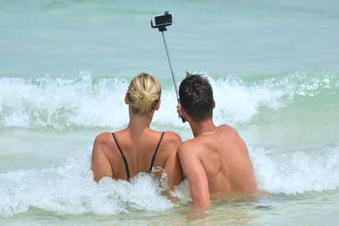 couple taking a picture with a selfie stick at the beach