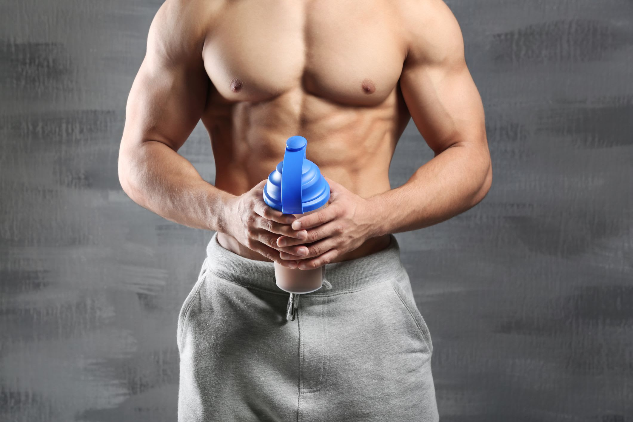man holding a blue bottle of protein drink