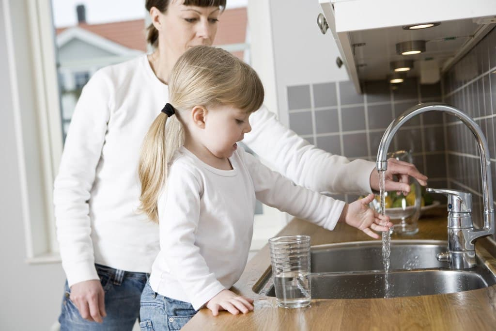 mother and a kid getting water from the faucet