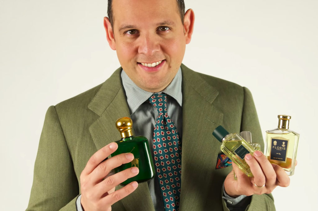 Man in green suit holding three bottles of cologne