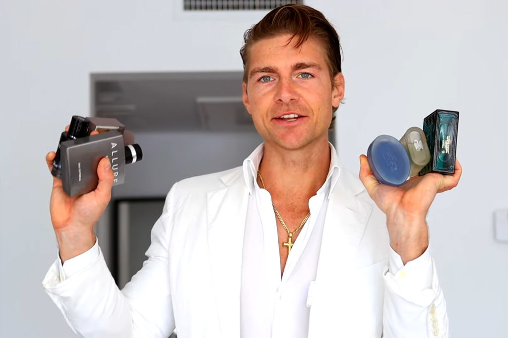 Jeremy Fragrance in white suit holding several bottles of colognes