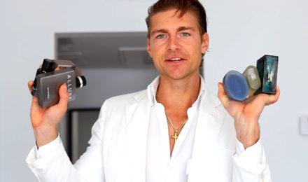 Jeremy Fragrance in white suit holding several bottles of colognes